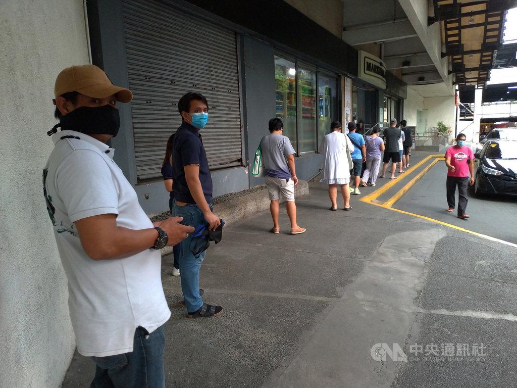 菲律賓武漢肺炎病例數持續攀升,馬尼拉民眾3日排隊等待進入超市採購時,遵照規定保持社交距離。中央社記者陳妍君馬尼拉攝 109年8月14日
