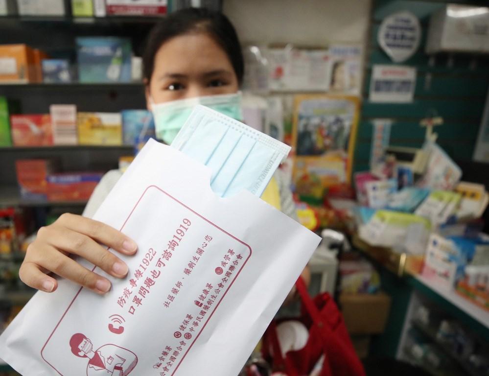 中央流行疫情指揮中心發言人莊人祥14日說,實名制口罩一片新台幣5元會延續到12月底。圖為民眾到藥局購買實名制口罩。(中央社檔案照片)