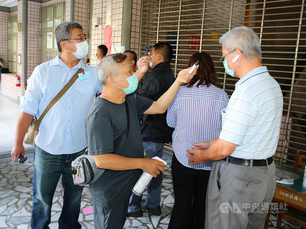 高雄市長補選15日投票,各投票所陸續出現排隊等候投票的民眾,工作人員一一為民眾量測額溫及進行手部清潔消毒。中央社記者郭日曉攝 109年8月15日