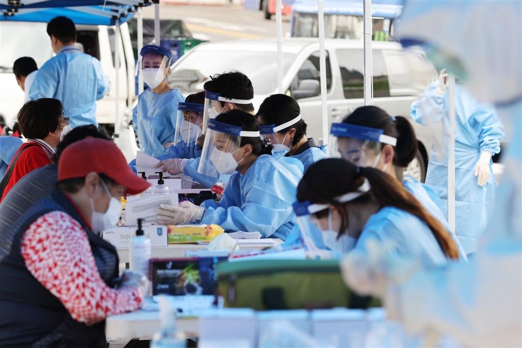 韓國首都圈疫情快速擴散,最嚴重的首爾市、京畿道防疫規範提升至第2階段。圖為韓國首爾南大門市場臨時篩檢站。(韓聯社)