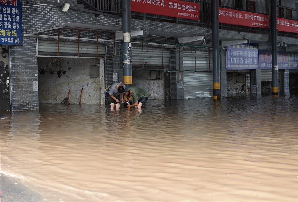 長江第4號洪水的洪峰15日才通過三峽庫區,中國水利部長江委水文局16日預測長江上游將再次形成「編號洪水」。圖為15日重慶渝中物流市場工作人員進行排水清淤。(中新社)