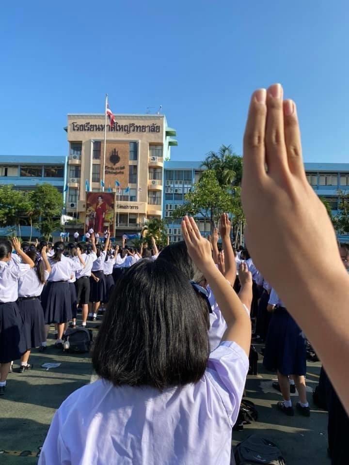 泰國近一個月以來的反政府示威抗議浪潮吹進高中校園,不少高中生在升旗時高舉三根手指的抗議手勢。(圖取自twitter.com/tanawatofficial)