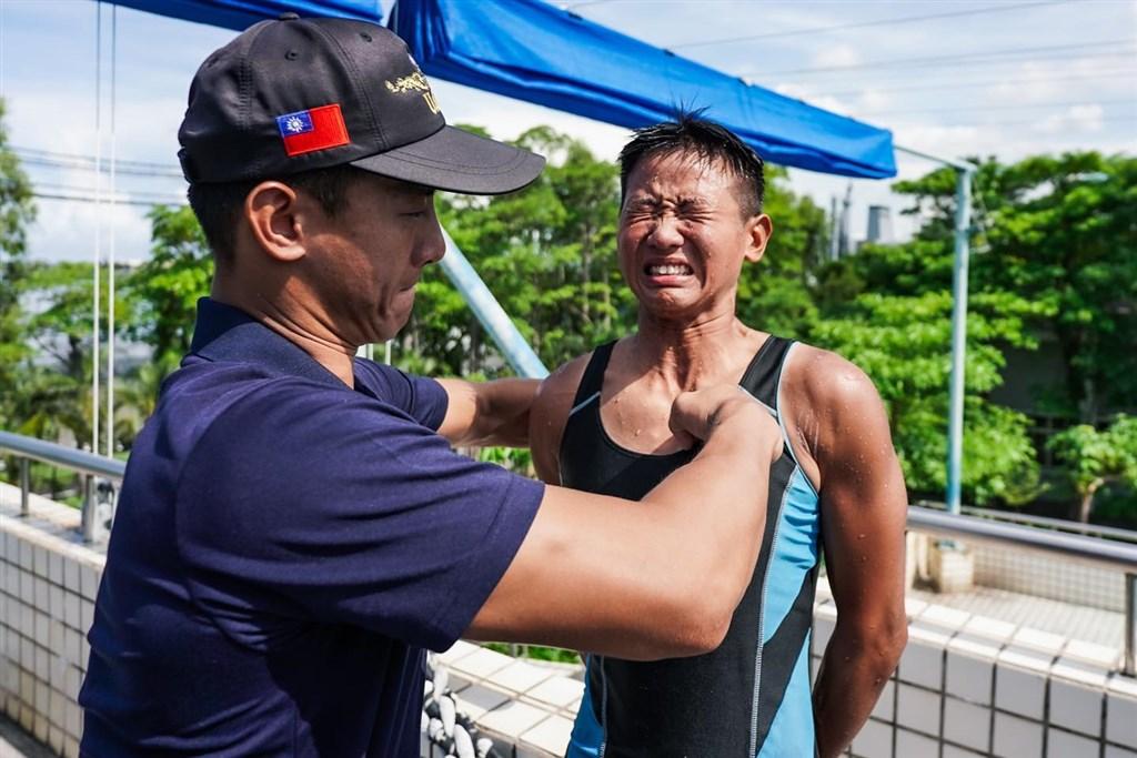 海軍水下作業大隊新成員任婕(右)近日通過訓練,由已是隊員的哥哥任毅親釘象徵訓練合格的金龍徽。(圖取自facebook.com/ROCNAVY.tw)