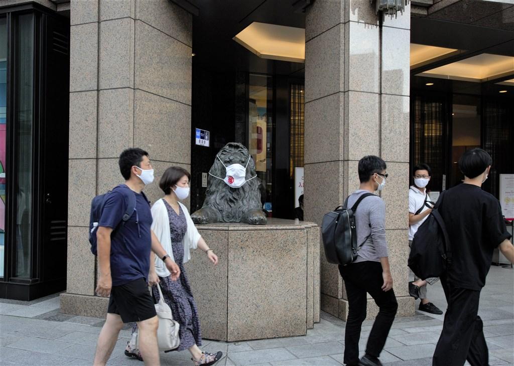 世界衛生組織秘書長譚德塞21日指出,全球對武漢肺炎大流行的掌控應能在2年之內達成,較遏止1918年流感大流行的速度快。圖為日本東京民眾戴口罩防疫,連店家門口的獅子雕塑也被戴上口罩。(中新社)