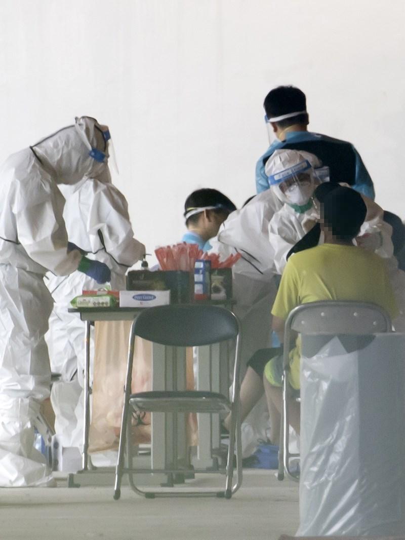 韓國23日新增397起確診病例,單日新增染疫人數創3月初以來新高;當局表示,韓國瀕臨武漢肺炎「全國性大流行」。圖為首爾一所學校內採檢站。(韓聯社)