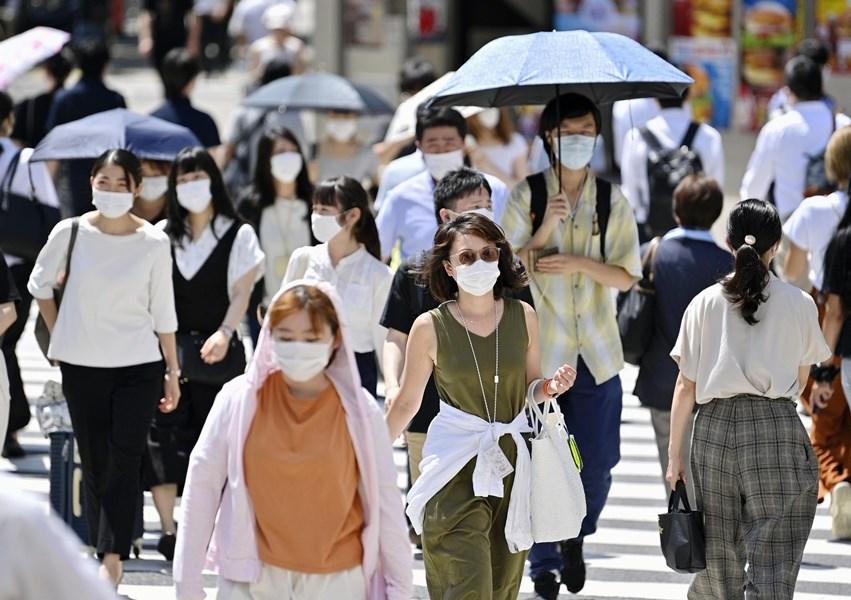 日本東京都23日單日新增212例武漢肺炎確診,累計病例數直逼2萬大關。圖為東京新宿街頭民民眾戴口罩。(共同社)