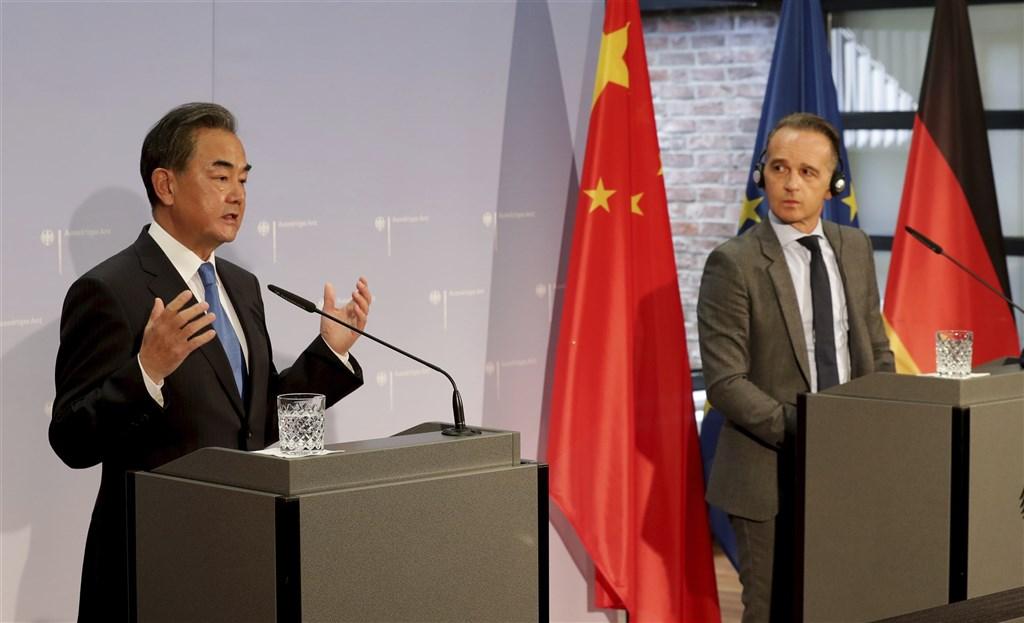 中國外長王毅(左)在德國威脅訪問台灣的捷克參議院議長維特齊要「付出沉重代價」,德國外長馬斯(右)與王毅共同出席聯合記者會時予以反擊。(美聯社)