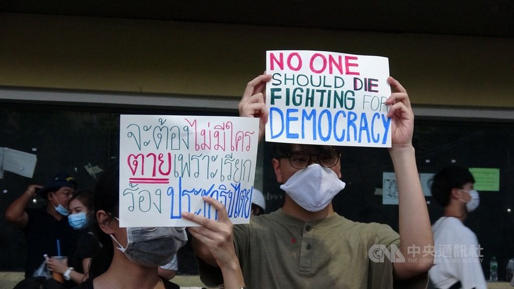 泰國眾議院史上首次將由委員會舉辦論壇,邀請正反兩方人士討論王室改革。圖為8月16日民主紀念碑的萬人抗議中高舉標語的泰國青年。(中央社檔案照片)