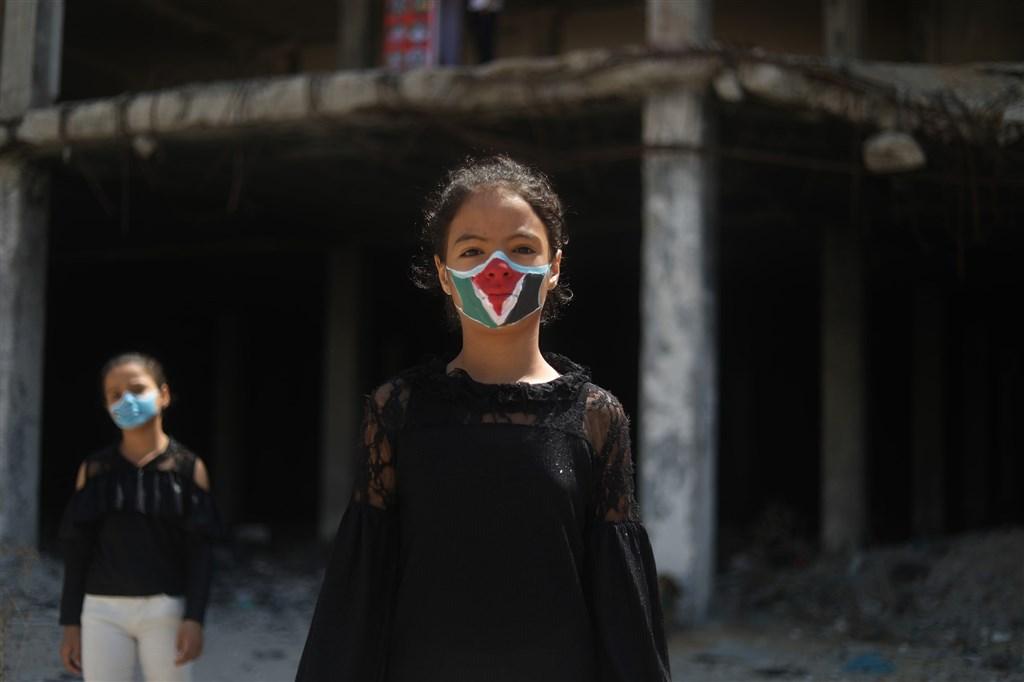 武漢肺炎疫情下封鎖的巴勒斯坦,藝術家替小女孩臉上彩繪面具。(安納杜魯新聞社)