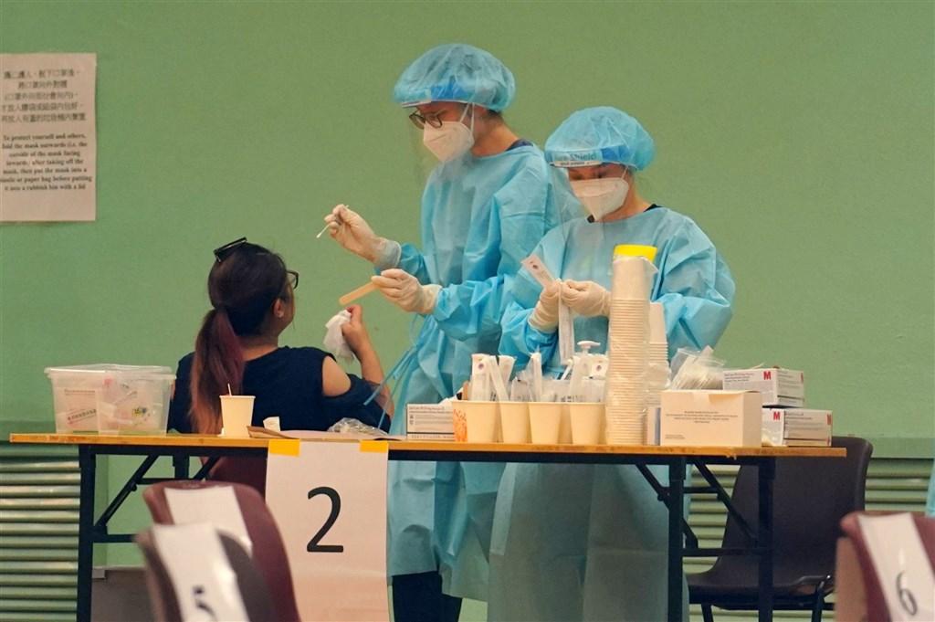 協助香港進行武漢肺炎病毒核酸檢測的中國大陸支援隊16日離港,他們總共檢測了178萬3000個樣本,發現確診病例與隱形患者共42人。圖為醫護人員採檢情形。(中新社)