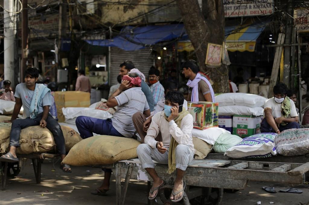 印度疫情惡化,總理要求7省市考慮短暫封鎖。圖為9日新德里街頭部分工人配戴口罩。(安納杜魯新聞社)