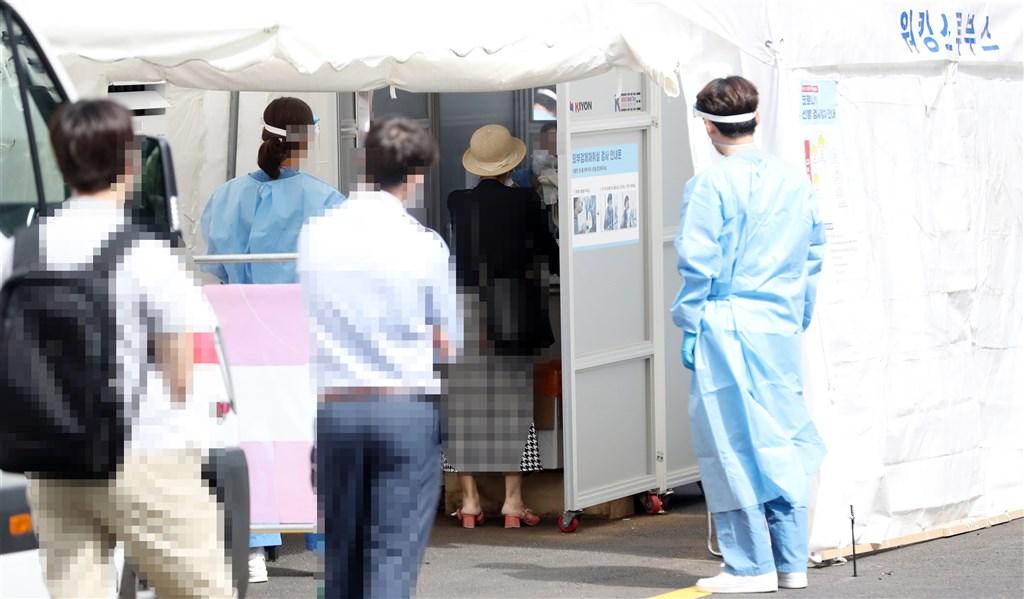 韓國武漢肺炎疫情持續擴散,防疫當局17日表示,近2週新增病例中高達26.4%感染途徑不明。圖為首爾民眾排隊接受病毒檢測。(韓聯社)