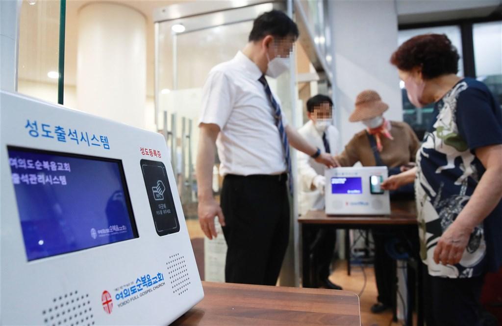 武漢肺炎疫情蔓延,韓國利用掃描QR code登記個資方式,管理高感染風險場所人員進出。圖為7月12日首爾民眾進入教會前用手機掃QR code。(韓聯社)