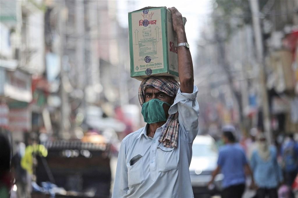世界衛生組織專家表示,全球每週約有5萬人染疫喪命,多到令人無法接受。圖為19日印度街頭。(美聯社)