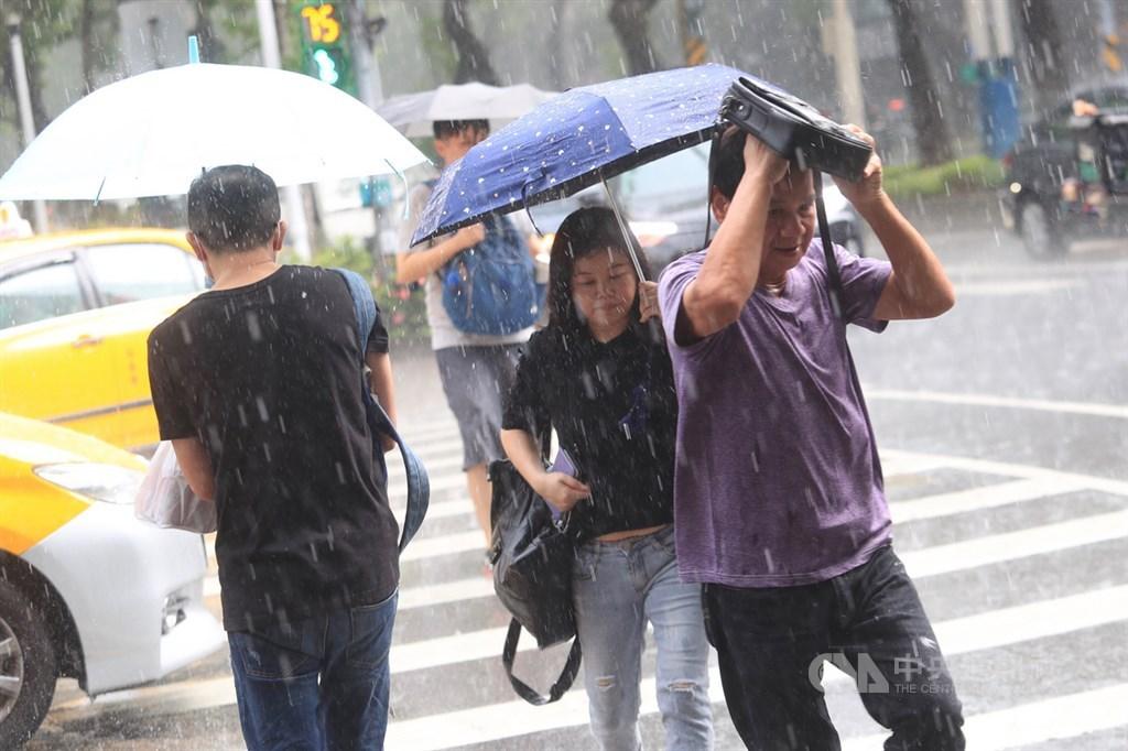 中央氣象局表示,20日鋒面通過及東北風增強,北部及東半部有局部短暫陣雨或雷雨。圖為18日台北市午後有雨,路上民眾急忙避雨。中央社記者吳家昇攝 109年9月18日