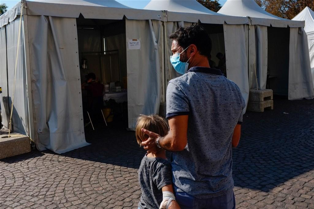 法國當局19日通報,境內過去24小時新增1萬3498人確診感染武漢肺炎,再創疫情爆發以來單日新高紀錄。圖為一名巴黎男子帶著小孩去做病毒檢測。(安納杜魯新聞社)