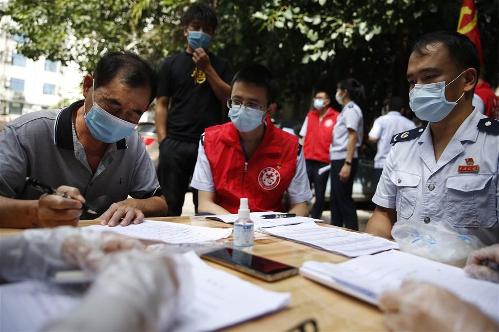 中國雲南省瑞麗市因緬甸境外移入疫情,雲南省19日召開疫情防控調度會議,要求各級、各地「全面進入戰時狀態」,強化邊境管控。圖為雲南省居民簽署承諾書,承諾家中無核酸檢測漏檢人員並遵守居家隔離規定。(中新社)