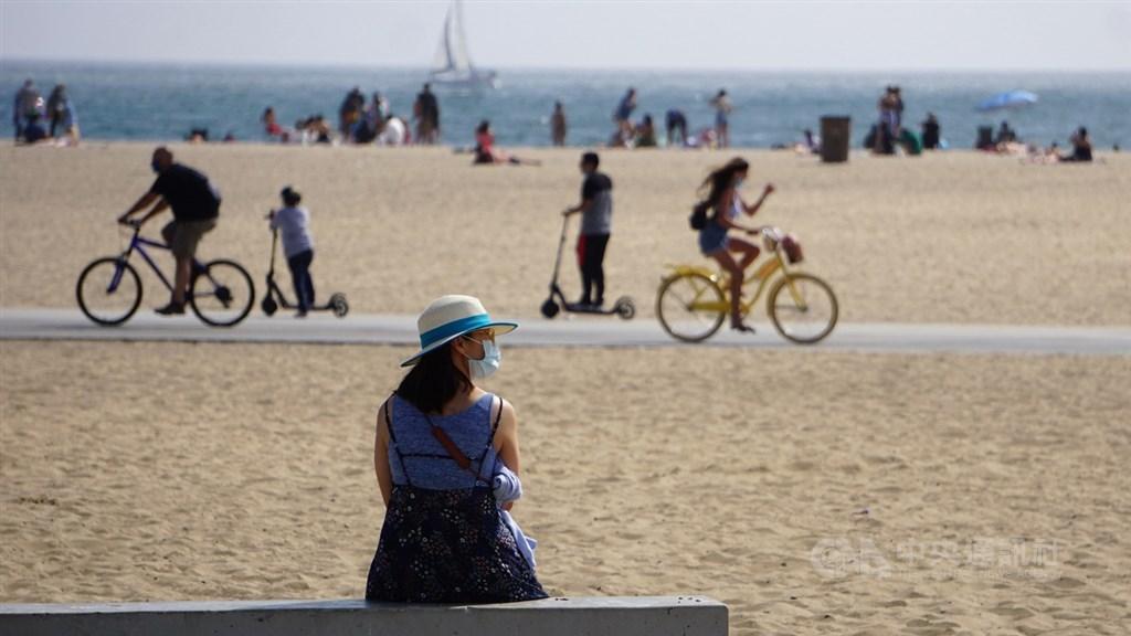 美國疫情未見改善,仍有不少民眾到海灘從事戶外活動。圖為7月29日洛杉磯聖塔蒙尼加海灘邊民眾戴口罩。(中央社檔案照片)