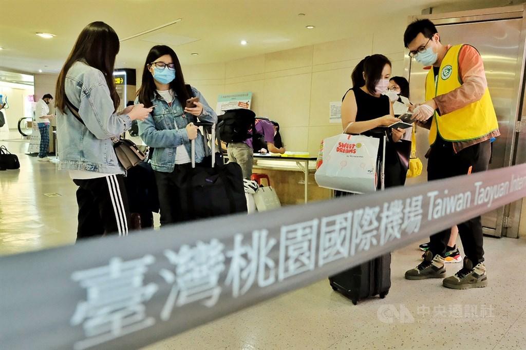 中央流行疫情指揮中心今天宣布,從菲律賓入境台灣普篩政策,改為入境有症狀採檢、無症狀不採。圖為桃園機場防疫人員對返國民眾疫調。(中央社檔案照片)