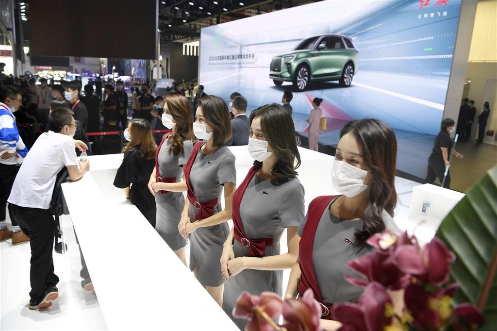 中國28日新增12例武漢肺炎確診病例。圖為同日登場的北京國際汽車展覽會工作人員配戴口罩。(共同社)