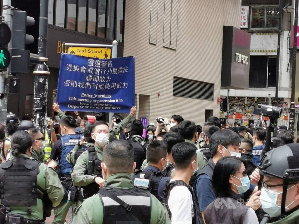 香港網友1日發起多區集會遊行,但至下午1時尚無大規模集結。銅鑼灣東角道一帶,有數百名防暴警察戒備,不時驅趕個別穿黑衣示威者。圖為防暴警察舉起藍旗,警告市民不要聚集。中央社記者張謙香港攝 109年10月1日