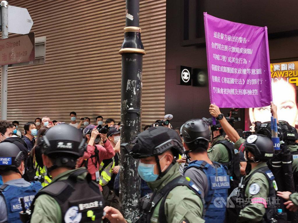 1日下午3時30分左右,銅鑼灣一帶還有一批示威者沒有離去,他們高叫「時代革命光復香港」口號,防暴警察舉起紫旗,警告他們已經違反國安法。中央社記者張謙香港攝 109年10月1日