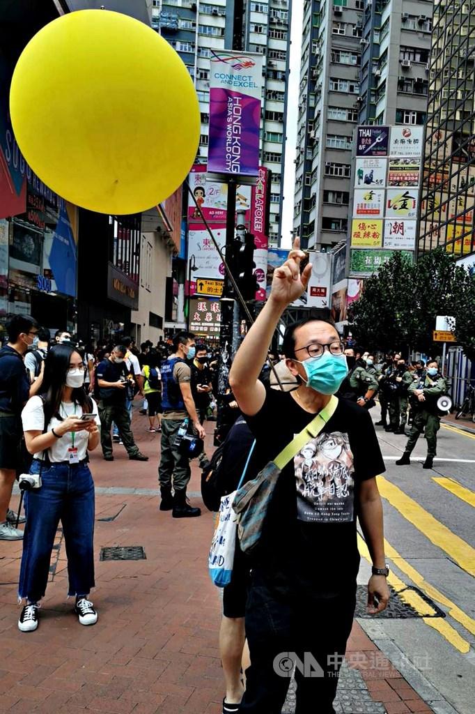 香港有網友發起1日於中國「國慶」當天在多區遊行,圖為銅鑼灣崇光(SOGO)百貨前,一名示威者高舉代表「反送中」運動的黃氣球。中央社記者張謙香港攝 109年10月1日
