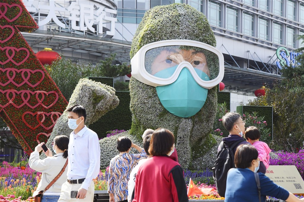 中國2日境內新增10例確診,均為境外移入。圖為北京街頭因應國慶而設置的戴口罩人形花壇。(共同社)