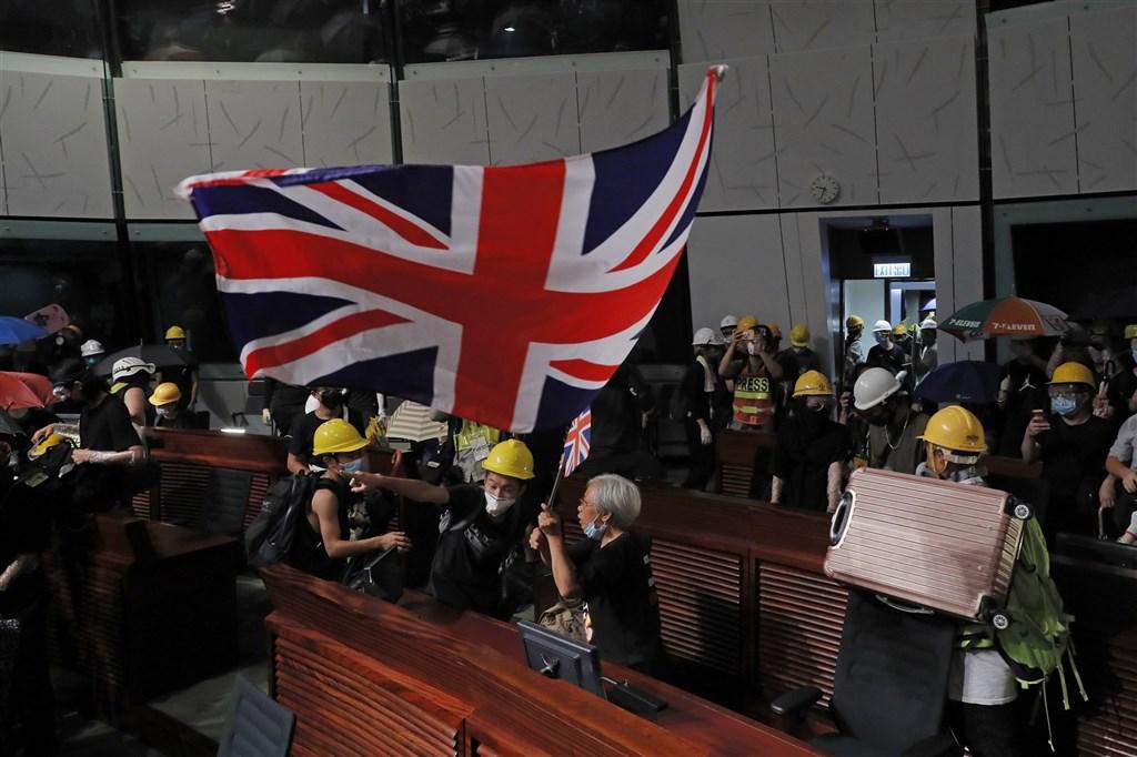 英國政府宣布,明年1月31日起開放擁有英國國民海外護照(BNO)資格的香港人民申請居留簽證。圖為反送中示威者2019年7月1日闖進香港立法會,高舉英國國旗。(美聯社)