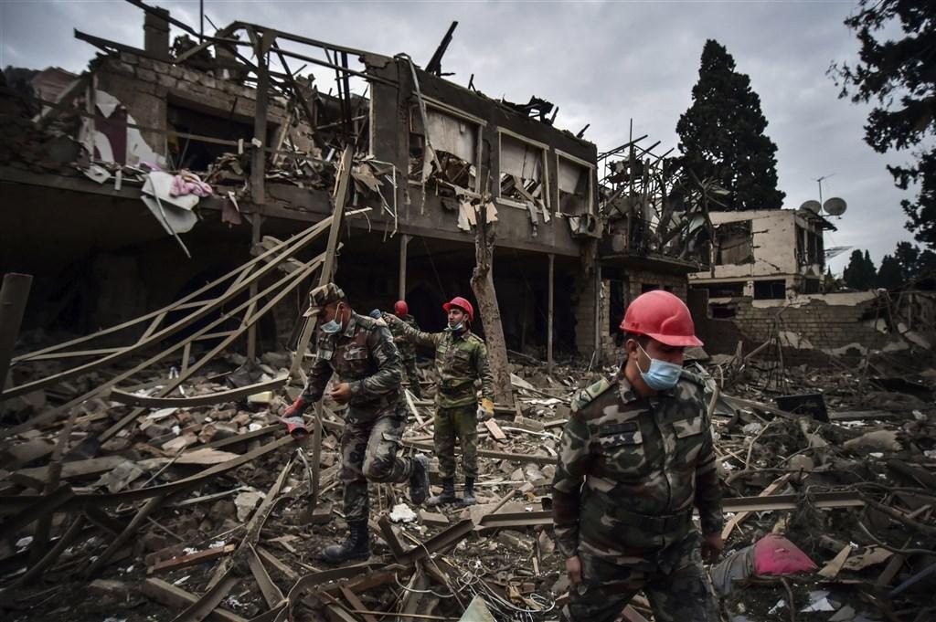 亞塞拜然11日表示,亞美尼亞部隊砲擊亞塞拜然第二大城甘賈,造成7人死亡和33人受傷。圖為亞塞拜然士兵及救難人員在甘賈搜尋生還者。(美聯社)