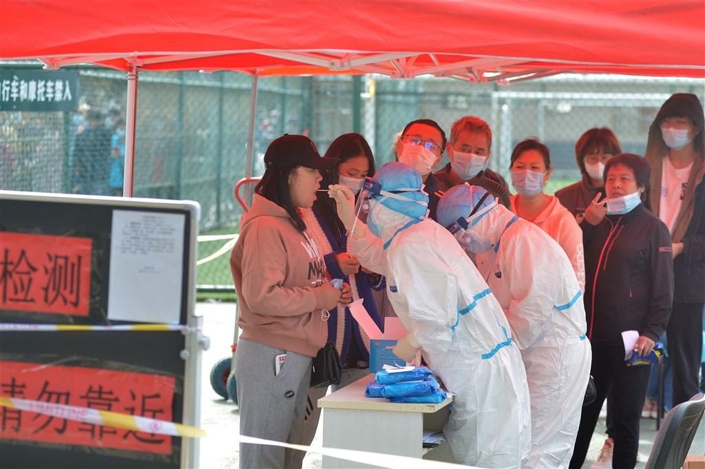 據官方通報,中國29日新增武漢肺炎確診病例25例,其中境外移入24例,本土1例是山東省青島市一名女護士,是在隔離醫院內遭到感染。圖為12日青島民眾排隊進行核酸檢測。(中新社)