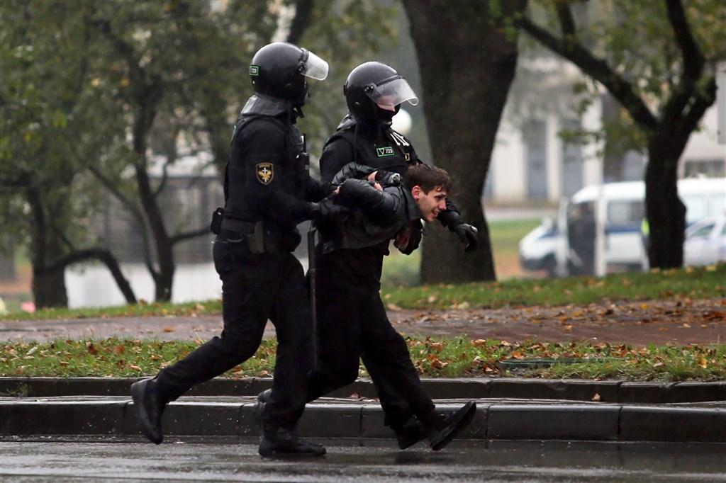 白俄羅斯首都明斯克11日數萬人再度上街抗議,要求執政長達26年的總統魯卡申柯下台,警方用水砲車、警棍和震撼彈驅散群眾且拘捕了數百人。圖為白俄羅斯警方逮捕示威者。(法新社)