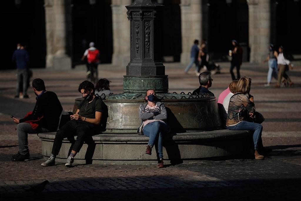 武漢肺炎疫情在全球各地捲土重來,歐洲各國為對抗疫情,14日紛紛祭出更嚴格的防疫管制,關閉酒吧、餐廳,並實施地方封鎖措施。圖為西班牙馬德里街頭民眾戴口罩(安納杜魯新聞社)