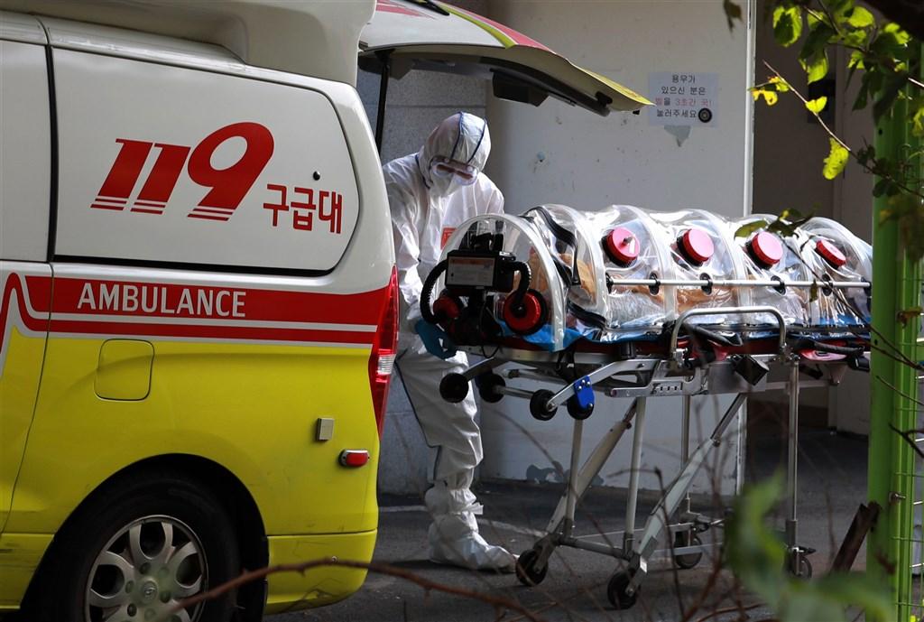 韓國釜山市北區一間療養醫院日前發生武漢肺炎群聚感染事件,其中一名確診員工曾搭車出席超過200人參與活動。圖為14日該院一名患者被送往其他醫院。(韓聯社)