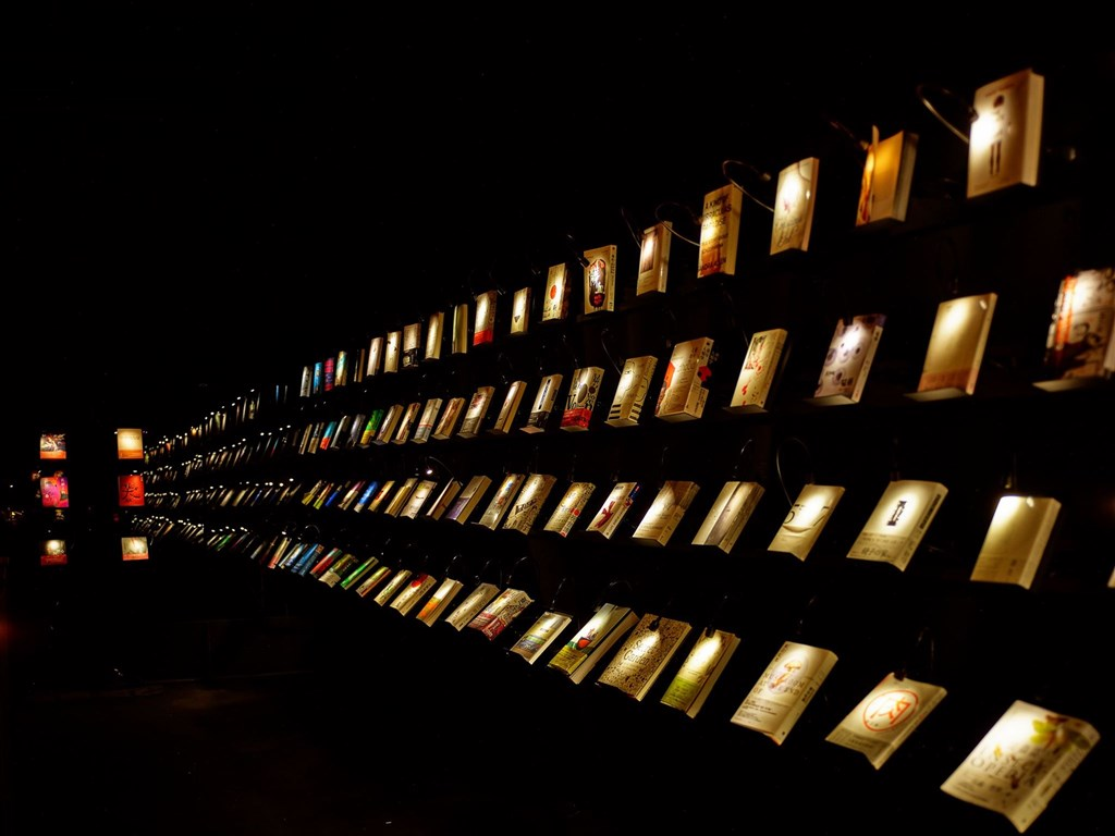 位於高雄駁二藝術特區的「無關實驗書店」打造一片漆黑的空間,微光只打在每本書和幾張閱讀桌上。(圖取自facebook.com/wuguanbooks)