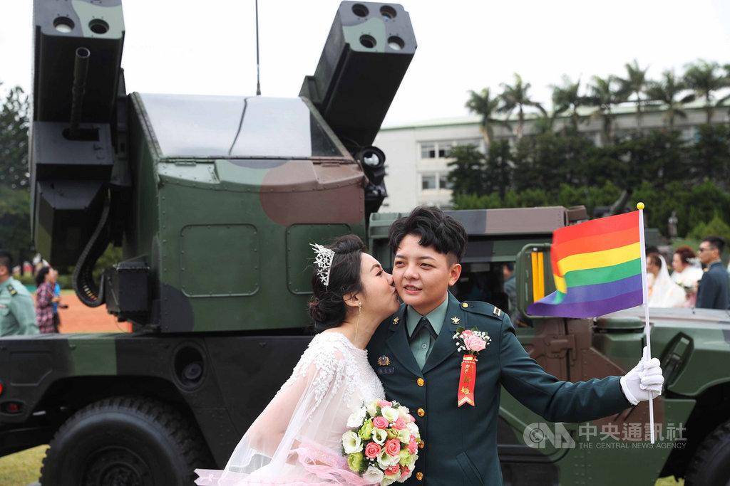 陸軍30日舉辦聯合婚禮,同婚官兵陳瑩宣(右)與妻子李沴稹(左)持彩虹旗在復仇者飛彈車前合影。中央社記者游凱翔攝 109年10月30日
