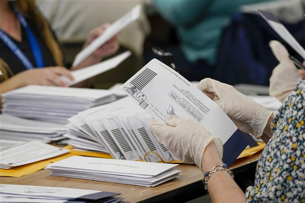 美國總統川普陣營9日提出訴訟,控賓州郵寄投票機制缺乏透明公開機制。圖為4日賓州計票人員從信封中抽出郵寄選票。(美聯社)