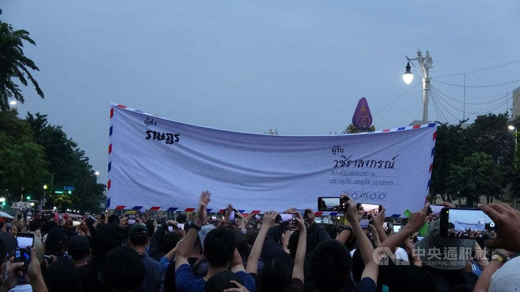 泰國反政府示威人士8日傍晚從民主紀念碑前遊行至大皇宮要遞交給泰王的信,圖為模擬信件的大型布條。中央社記者呂欣憓曼谷攝 109年11月8日