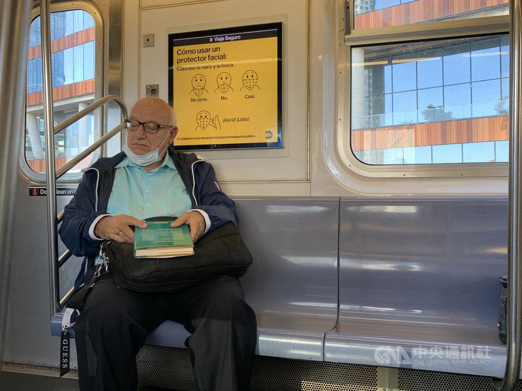 2019冠狀病毒疾病疫情爆發後,紐約地鐵以車廂廣告宣導如何正確配戴口罩,但仍有乘車民眾口罩未遮住口鼻。中央社記者尹俊傑紐約攝 109年11月18日