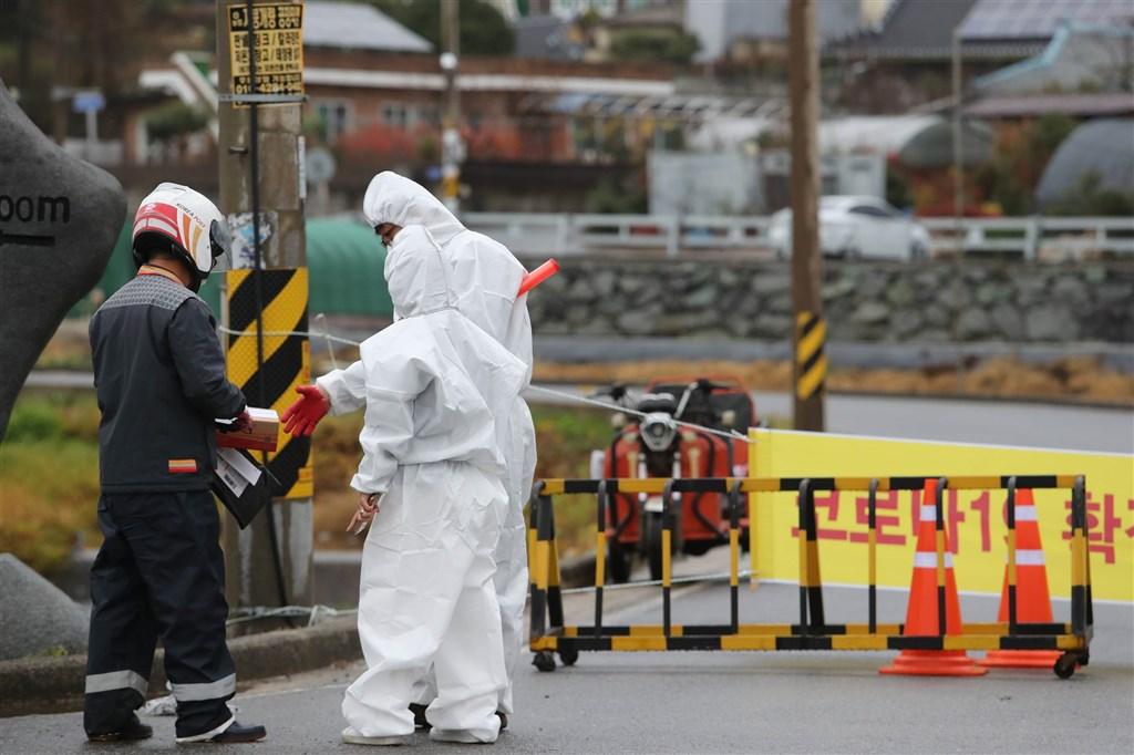 韓國境內單日確診感染武漢肺炎連續2天破300例,當局考慮再提高防疫等級。圖為全羅南道一村莊因封鎖而由檢疫人員收外送包裹。(韓聯社)