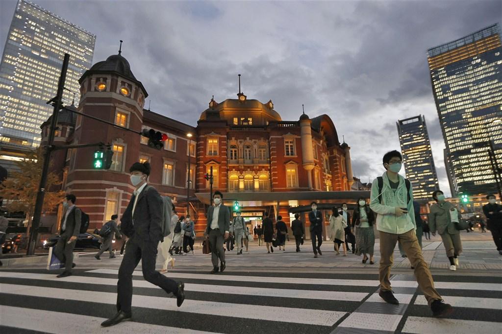 日本境內武漢肺炎疫情持續升溫,東京都20日新增522例確診病例,連續2天單日逾500例。圖為路人在東京站附近行走。(共同社)