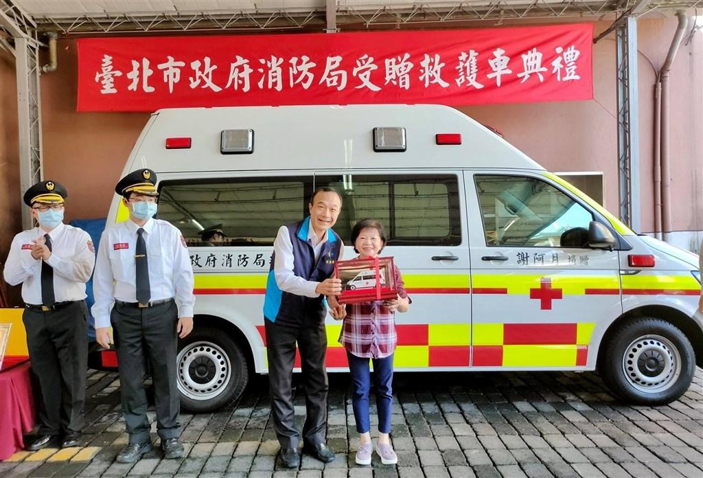 台北市消防局19日舉辦捐贈典禮,由副局長畢幼明(右2)接受開家庭理髮店的謝阿月(右1)捐贈的一輛高頂救護車。(圖取自facebook.com/119.Taipei)