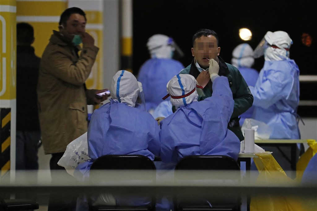 上海浦東機場接連傳出本土確診病例後,截至23日下午2時30分,已有4成航班取消。圖為相關人員正在進行核酸檢測。(中新社)