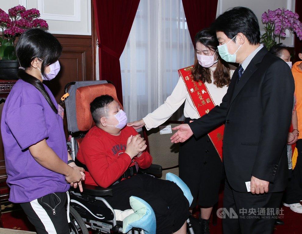 副總統賴清德(右)23日在總統府接見第23屆大愛獎得獎人及其身心障礙子弟,肯定得獎人照顧身心障礙子女的付出。中央社記者鄭傑文攝 109年11月23日