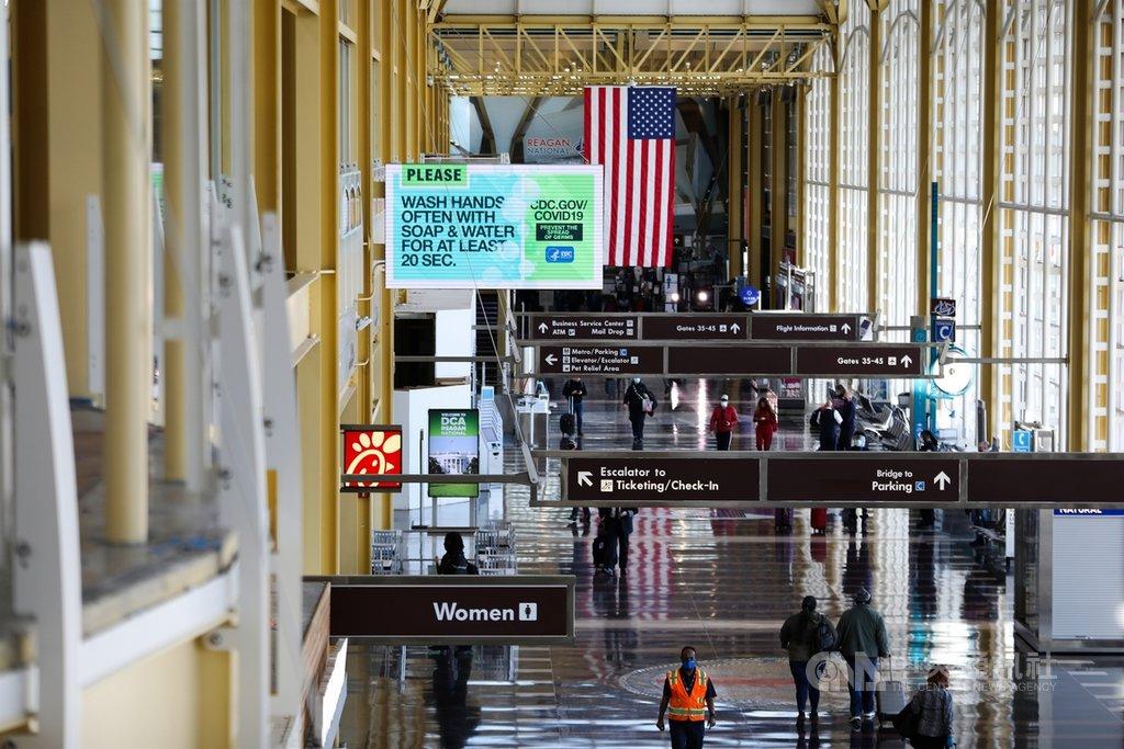 美國雷根國家機場25日出現感恩節假期返鄉人潮,機場看板打上呼籲旅客用肥皂勤洗手的宣導標語。中央社記者徐薇婷華盛頓攝  109年11月26日