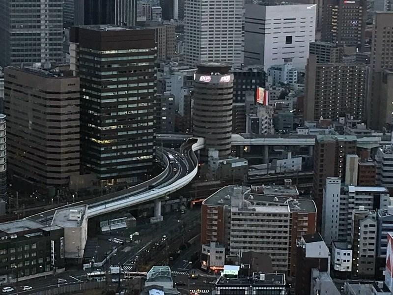 日本大阪阪神高速公路穿越「門塔大廈」(圖中圓形建物),形成街景中的一幅奇特畫面。(讀者提供)