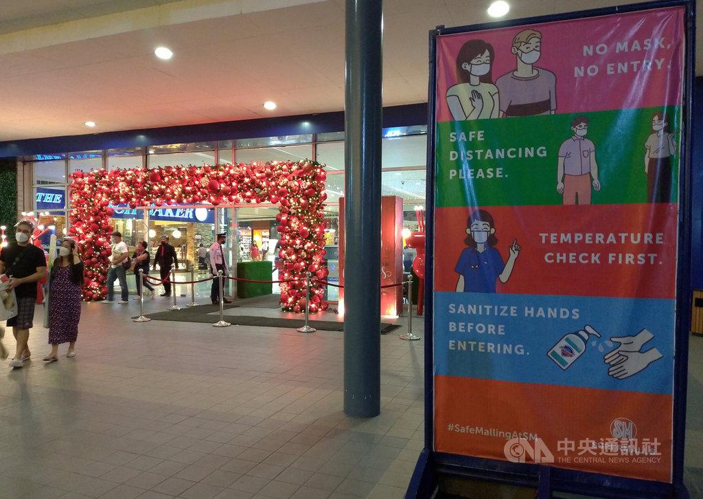 菲律賓武漢肺炎每日新增病例仍在攀升,安格利斯市一處購物商場29日以看板提醒民眾戴口罩並保持社交距離。中央社記者陳妍君班巴加省攝 109年11月30日