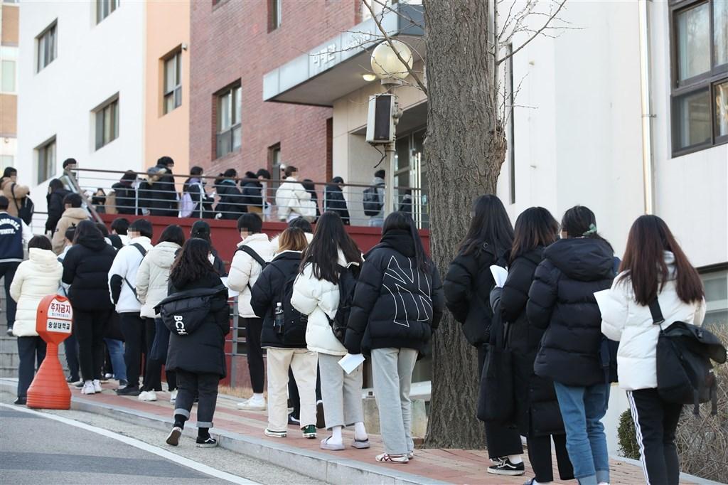 韓國專家指出,剛結束大學聯考的高3考生「出關」,將成疫情變數。圖為韓國考生排隊量體溫、進考場。(韓聯社)