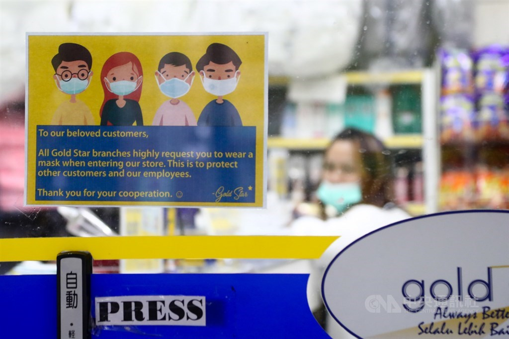 過去短短10天就有60多例移工確診武漢肺炎,指揮中心指揮官陳時中6日說,將持續培養病毒以了解有無傳染可能性。圖為商家門口貼英文告示,提醒民眾進入店內需戴口罩。(中央社檔案照片)