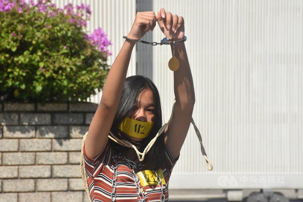 泰國抗議人士10日早上在聯合國亞太經社委員會位於曼谷的總部外,呼籲廢除刑法112條。抗議人士象徵性戴上手銬和貼膠布,代表法律限制泰國人民的言論自由。中央社記者呂欣憓曼谷攝 109年12月10日